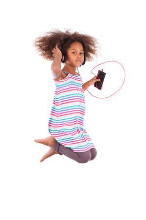 Little african american girl jumping and listening to music, isolated on white background - Black people photo