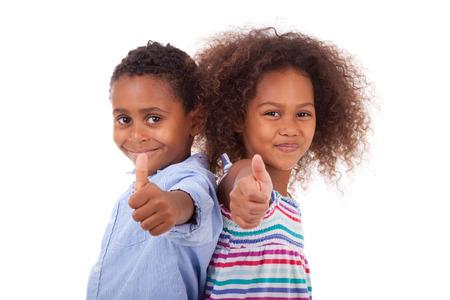 Muchacho afroamericano y una chica haciendo pulgares arriba gesto, aislados en fondo blanco - los negros Foto de archivo