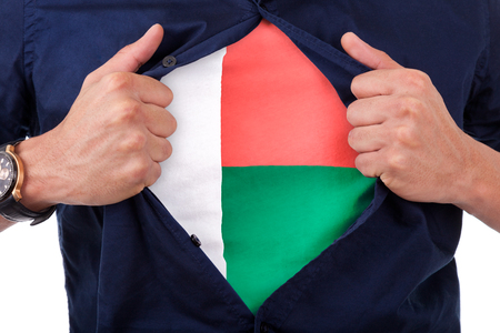 national hero: Young sport fan opening his shirt and showing the flag his country Madagascar,  Malagasy flag Stock Photo