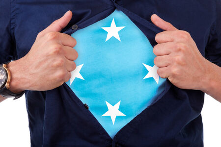 national hero: Young sport fan opening his shirt and showing the flag his country Micronesia, Micronesian flag