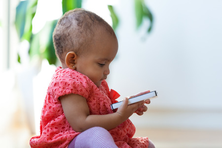 african american infant: Portrait of little African American little girl holding a mobile phone - Black people