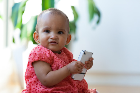 Portrait of little African American little girl holding a mobile phone - Black people photo