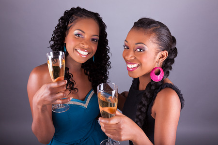 Young beautiful African American womans holding a glass of champagne Stock Photo