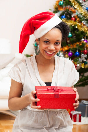 south american ethnicity: Young African American woman holding a gift box - Black people