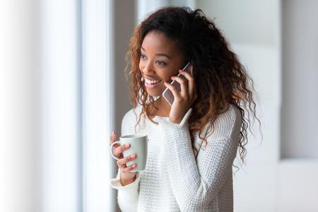 celulas humanas: African American mujer hablando por un tel�fono m�vil - los negros Foto de archivo