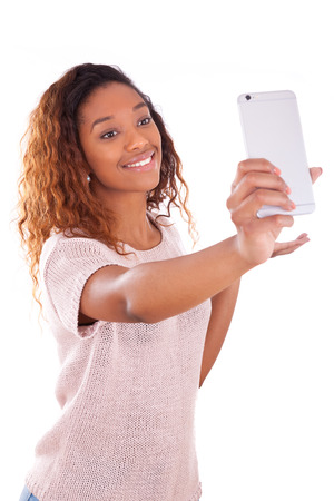 are taking: Young African American woman taking a selfie - self portrait - Black teenager people