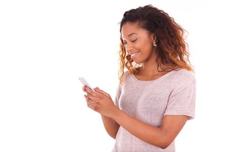 celulas humanas: Mujer joven afroamericana que env�a un mensaje de texto en su tel�fono inteligente Foto de archivo