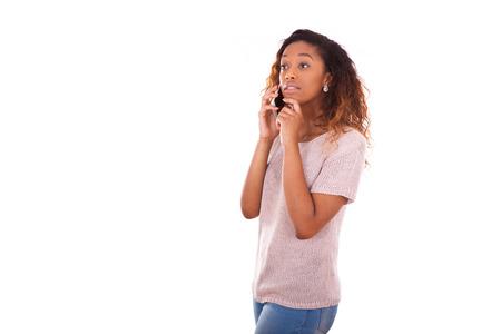 dudando: Joven mujer afroamericana haciendo una llamada telefónica en su teléfono inteligente - gente adolescente negro