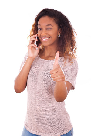 Young African American woman making a phone call on her smartphone making thumbs up gesture photo