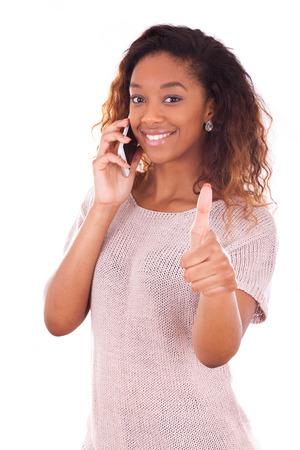llamando: Joven mujer afroamericana haciendo una llamada telefónica en su teléfono inteligente haciendo pulgares arriba gesto