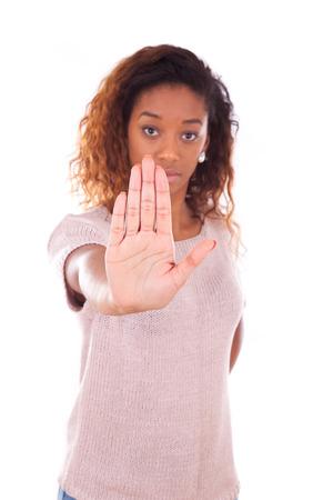 Ongelukkige jonge Afro-Amerikaanse stopbord met haar hand palm op een witte achtergrond