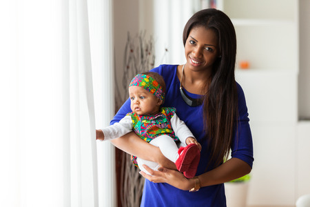 afro caribbean: Young african american mother holding with her baby girl Stock Photo