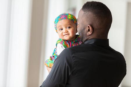 padres: Padre afroamericano joven que sostiene con su bebé