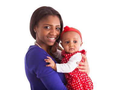 mama e hija: Madre afroamericana joven que sostiene con su beb� aislado en el fondo blanco Foto de archivo