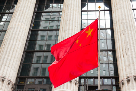 Chinese flag floating in front of a goverment building Stock Photo