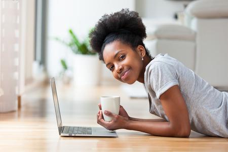 mujeres africanas: Mujer afroamericana con un ordenador port�til en su sala de estar - los negros Foto de archivo
