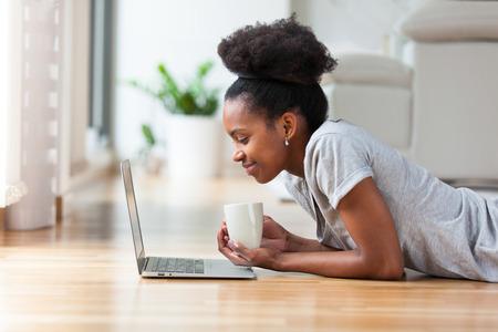 femme africaine: Femme afro-am�ricaine utilisant un ordinateur portable dans son salon - Noirs Banque d'images