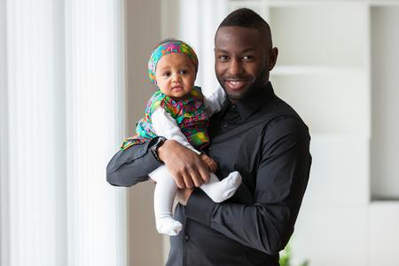 Padre afroamericano joven que sostiene con su bebé