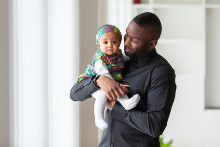 그녀의 아기 소녀와 함께 들고 젊은 아프리카 계 미국인 아버지