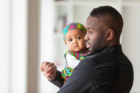 그녀의 여자 아기를 들고 젊은 아프리카 계 미국인 아버지 스톡 콘텐츠