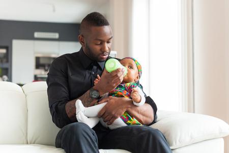 아기 병에 그녀의 아기 소녀에 우유를주는 젊은 아프리카 계 미국인 아버지