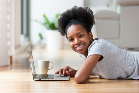 afro caribbean: African American woman using a laptop in her living room