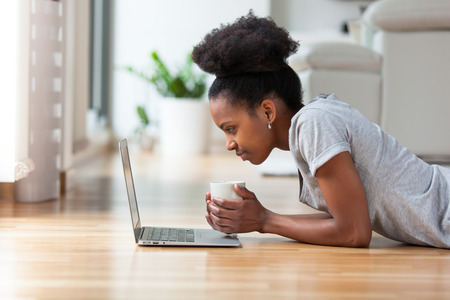 femmes souriantes: Femme afro-américaine utilisant un ordinateur portable dans son salon Banque d'images