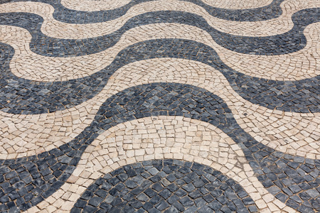 Typical portuguese cobblestone hand-made pavement calçada in Lisbon, Portugal