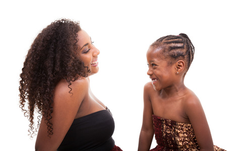 plaits: African american mother with her daughter looking and smiling at each other, isolated on white background Stock Photo