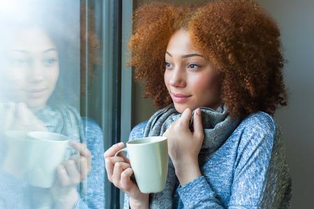 熱い飲み物を飲むと、窓から見てブラック アフリカ系アメリカ人 10 代の少女