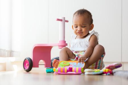 mignonne petite fille: Portrait de petite afro-américaine petite fille assise sur le sol et jeu - les Noirs