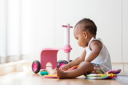 Portrait of little African American little girl sitting on the floor and playing  - Black people Foto de archivo