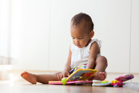black kid: Portrait of little African American little girl sitting on the floor and playing  - Black people Stock Photo