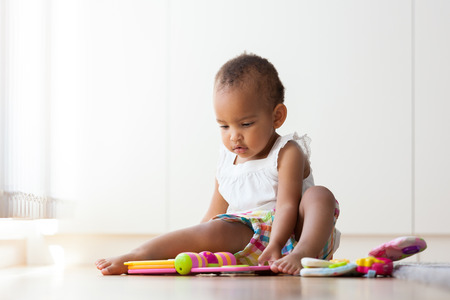 baby sitting: Portrait of little African American little girl sitting on the floor and playing  - Black people Stock Photo