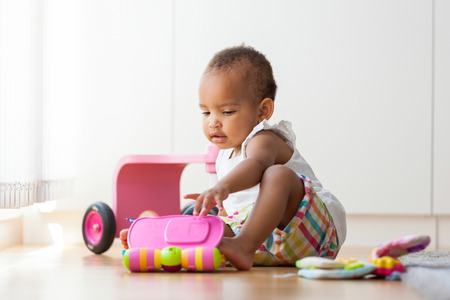 Portrait of little African American little girl sitting on the floor and playing  - Black people 스톡 콘텐츠