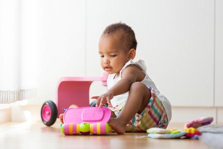 bebes niñas: Retrato de la pequeña niña estadounidense sentado en el suelo y de juego - los negros