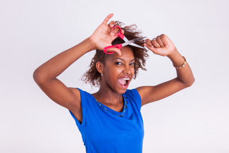 afro americans: Young African American woman cutting her frizzy afro hair with scissors - Black people