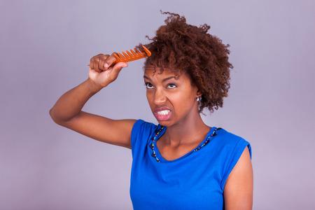 Mujer joven del afroamericano que se peina el pelo muy rizado afro - los negros Foto de archivo - 43217934
