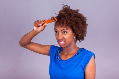afro curly hair: Young African American woman combing her frizzy afro hair - Black people