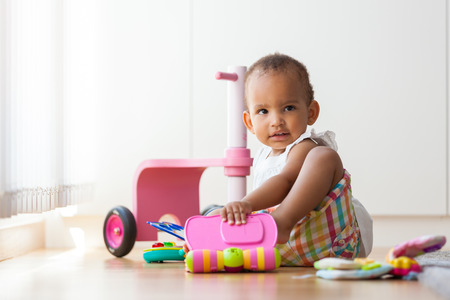 children learning: Portrait of little African American little girl sitting on the floor and playing  - Black people Stock Photo