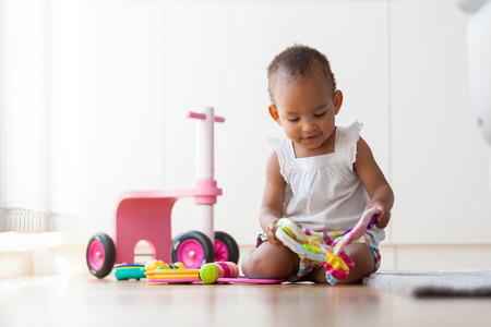 juguetes: Retrato de la peque�a ni�a estadounidense sentado en el suelo y de juego - los negros