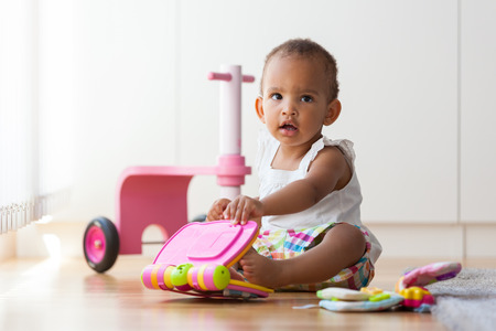 discovering: Portrait of little African American little girl sitting on the floor and playing  - Black people Stock Photo