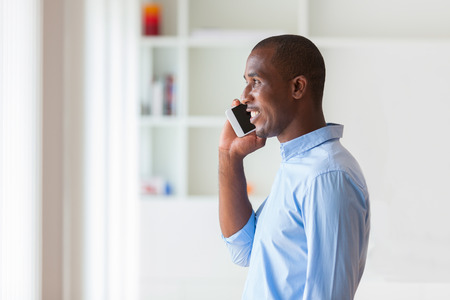 south american: Portrait of a young African American business man using a mobile phone - Black people Stock Photo