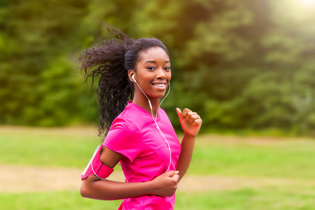 active listening: African american woman runner jogging outdoors - Fitness, people and healthy lifestyle