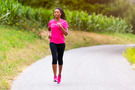 earphone: African american woman runner jogging outdoors - Fitness, people and healthy lifestyle