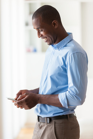 joyful businessman: Portrait of a young African American business man using a mobile phone - Black people Stock Photo