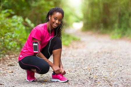 フィットネス: アフリカ系アメリカ人の女性ランナーの靴ひも - フィットネス、人や健康的なライフ スタイルを引き締め