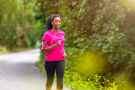 African american woman runner jogging outdoors - Fitness, people and healthy lifestyle. Stock Photo