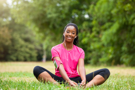 active listening: African american woman jogger stretching  - Fitness, people and healthy lifestyle Stock Photo