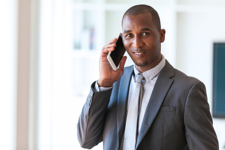 phone business: Portrait of a young African American business man using a mobile phone - Black people Stock Photo